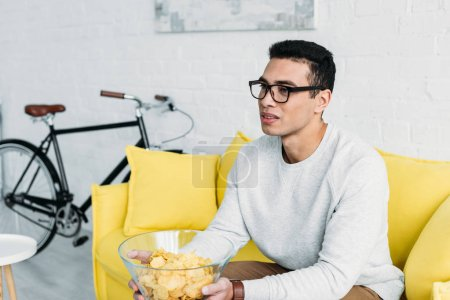 Photo for Young mixed race man sitting on yellow sofa and holding bowl of chips - Royalty Free Image