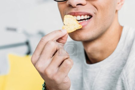 cropped view of man in white sweatshirt eating chips