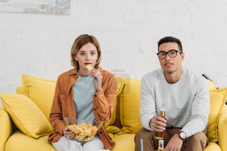 Photo for Interracial couple enjoying snacks and drinks while sitting on yellow sofa - Royalty Free Image