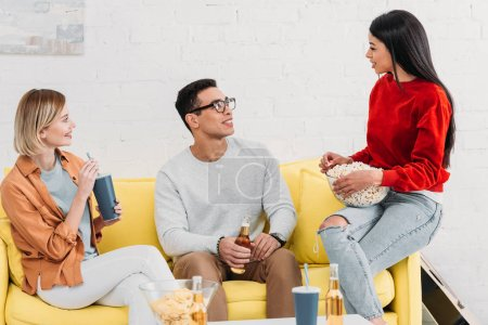 Photo for Smiling multicultural friends enjoying drinks and snacks while sitting on yellow sofa - Royalty Free Image
