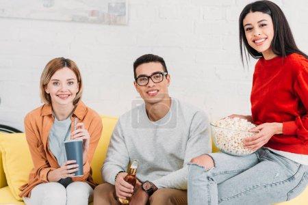 Foto de Sonrientes a amigos multiétnicas con bebidas y aperitivos mientras está sentado en el sofá amarillo - Imagen libre de derechos
