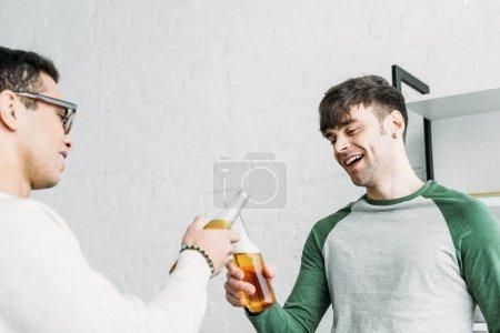 Foto de Amigos multiculturales sonriendo y tintineo de botellas de cerveza - Imagen libre de derechos