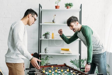 Photo for Multicultural friends playing table football in living room - Royalty Free Image