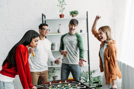 Photo for Multicultural friends having fun, girls playing table football while men watching their game - Royalty Free Image