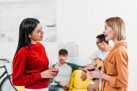 Photo for Multicultural friends holding glasses and talking while men sitting on yellow sofa - Royalty Free Image