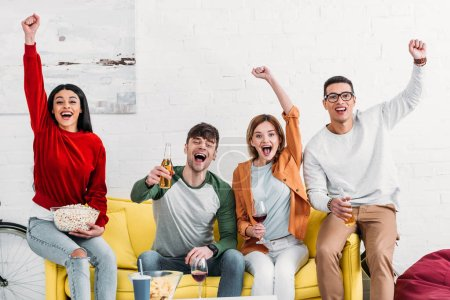 Photo for Multicultural excited friends drinking beer and wine and eating snacks at home party - Royalty Free Image