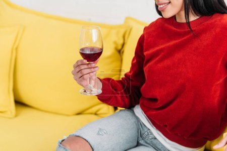 Afrikanische Amerikanerin sitzt auf gelbem Sofa und hält ein Glas Wein in der Hand