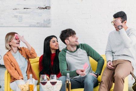 multiethnische Freunde haben Spaß auf der Heimatparty und kleben Aufkleber an die Stirn