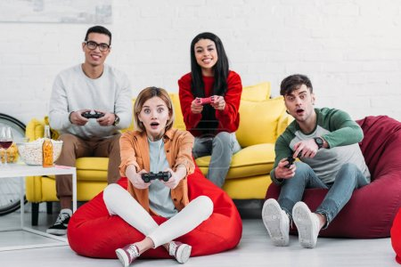 Photo for Happy multicultural friends playing video game and enjoying drinks and snacks at home party - Royalty Free Image