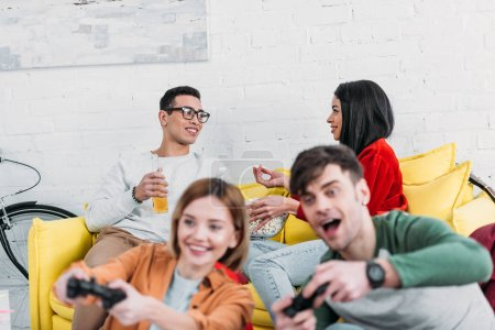 Photo for Happy multicultural friends having fun at home party, playing video game and enjoying drinks and snacks - Royalty Free Image