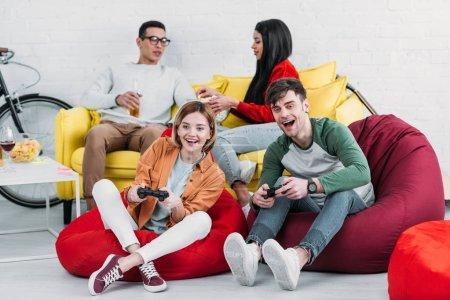 Foto de Feliz fiesta multiculturales amigos jugando videojuegos y disfrutar bebidas y aperitivos en el hogar - Imagen libre de derechos