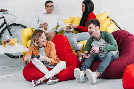 Photo pour Heureuse fête multiculturelles amis jouer des jeux vidéo et profiter de boissons et de collations à la maison - image libre de droit
