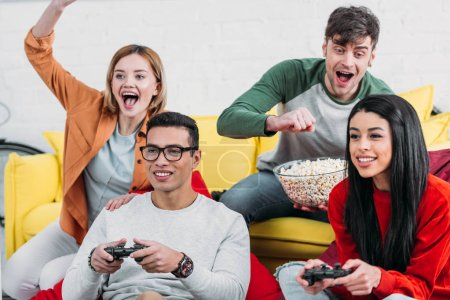 Photo for Multicultural friends having fun at home party, playing video game and enjoying drinks and snacks - Royalty Free Image