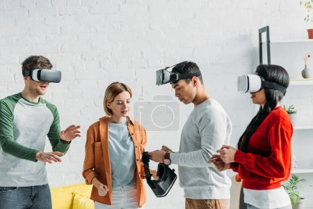 Photo for Multiethnic friends putting on virtual reality headsets - Royalty Free Image