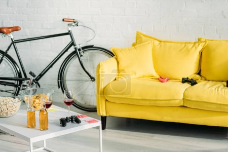 living with comfortable yellow sofa and table with drinks and snacks