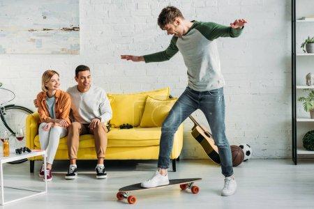 Foto de Amigos multiculturales sentados en un sofá amarillo y mirando a un amigo montando longboard - Imagen libre de derechos