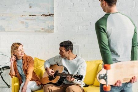 Foto de Hombre guapo ladinos tocando la guitarra para los amigos multiculturales - Imagen libre de derechos