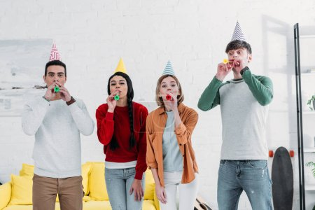 Photo for Multiethnic friends in multicolored paper hats having fun at home party - Royalty Free Image