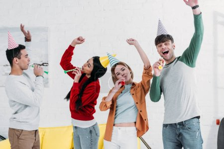 Photo for Cheerful multiethnic friends in multicolored paper hats having fun at home party - Royalty Free Image