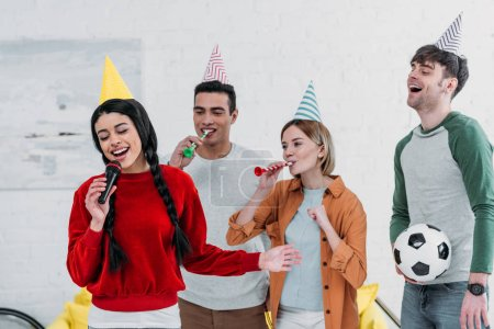 Photo for Multicultural friends in colorful paper hats singing karaoke at home party - Royalty Free Image