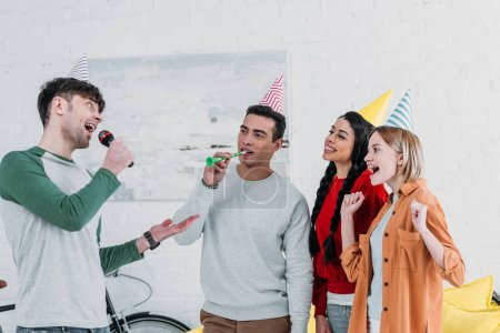 Photo for Happy multicultural friends in colorful paper hats singing karaoke at home party - Royalty Free Image