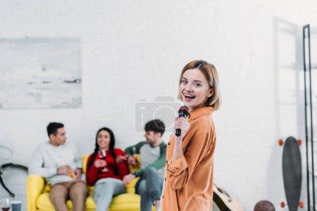 Foto de Niña bonita cantando karaoke mientras multiétnicos amigos disfrutar de bebidas en el sofá amarillo - Imagen libre de derechos