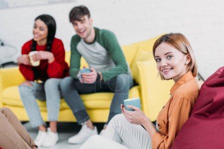 Foto de Felizes amigos multiculturales tomando café sentado en la sala de estar - Imagen libre de derechos