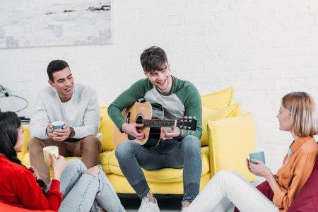 Foto de Guapo Alegre tocando la guitarra con amigos multiculturales - Imagen libre de derechos