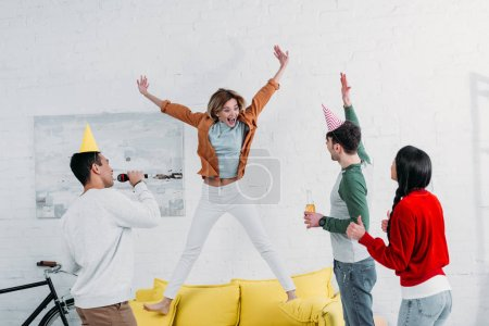 Photo for Cheerfull girl jumping on yellow sofa while multicultural friends singing karaoke and dancing - Royalty Free Image