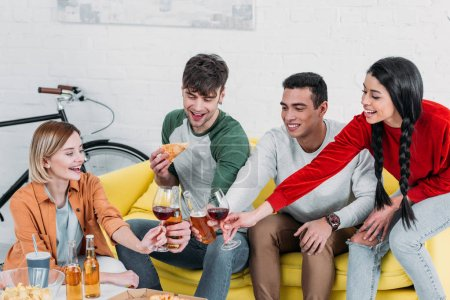 Photo for Multicultural friends eating pizza and enjoying drinks at home party - Royalty Free Image