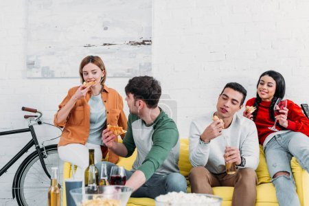 Photo for Happy multicultural friends eating pizza and enjoying drinks at home party - Royalty Free Image
