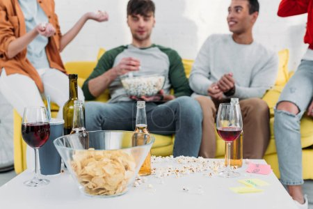Photo for Multicultural friends having fun end enjoying snacks and drinks at home party - Royalty Free Image