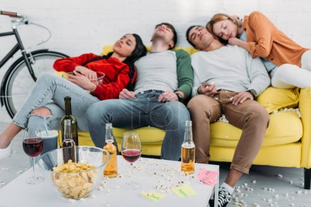 Photo for Exhausted multicultural friends sleeping on yellow sofa in living room - Royalty Free Image
