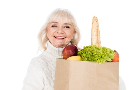 Photo for Cheerful senior woman holding paper bag with groceries isolated on white - Royalty Free Image