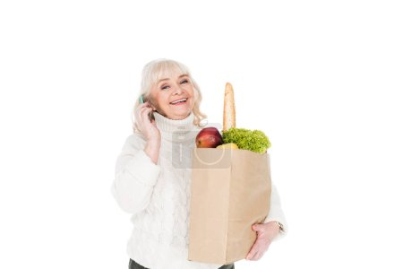 Photo for Happy senior woman holding paper bag with groceries isolated on white - Royalty Free Image
