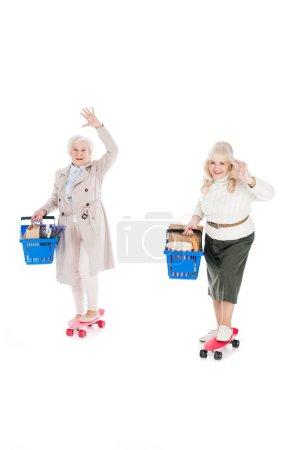 Photo pour Heureux seniors femmes équitation penny planches et tenant des paniers idolâtrés sur blanc - image libre de droit