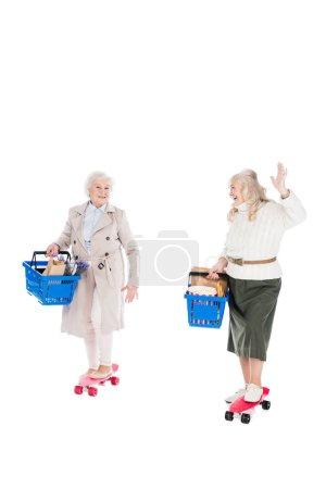 Photo pour Heureux senior femme équitation penny conseil et agitant la main à un ami tenant panier idolâtré sur blanc - image libre de droit