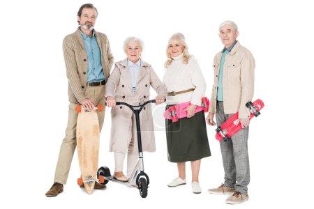 Photo pour Joyeuses retraités debout avec planches à roulettes près de femmes sur scooter isolé sur blanc - image libre de droit
