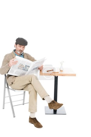 Photo for Senior man reading newspaper while sitting on chair with crossed legs isolated on white - Royalty Free Image