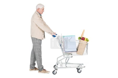 Photo for Retired man with grey hair walking with shopping cart isolated on white - Royalty Free Image