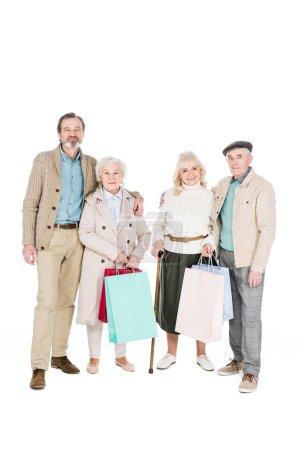 Foto de Amigos jubilados alegres sosteniendo bolsas y pie aislado en blanco - Imagen libre de derechos