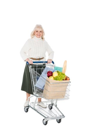 Photo for Happy senior woman holding shopping cart with shopping bags and paper bag with groceries isolated on white - Royalty Free Image