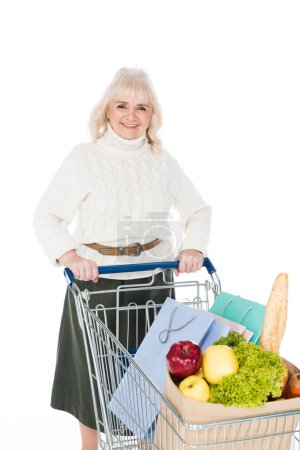 Photo for Smiling senior woman holding shopping cart with shopping bags and paper bag with groceries isolated on white - Royalty Free Image