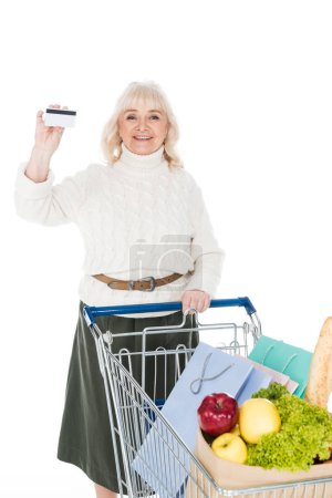 Photo for Cheerful senior woman holding credit card near shopping trolley isolated on white - Royalty Free Image