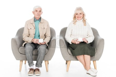 Photo for Happy retired husband and wife holding cups with tea while sitting in armchairs isolated on white - Royalty Free Image