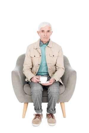 retired man sitting in armchair with cup of tea isolated on white