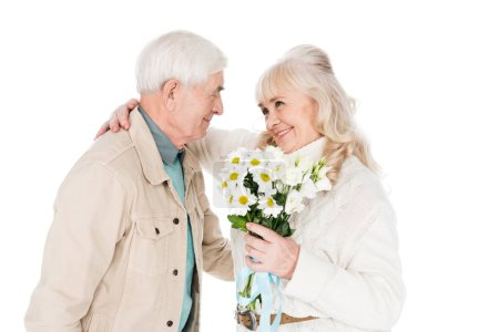 Photo for Cheerful senior man giving flowers to happy wife isolated on white - Royalty Free Image