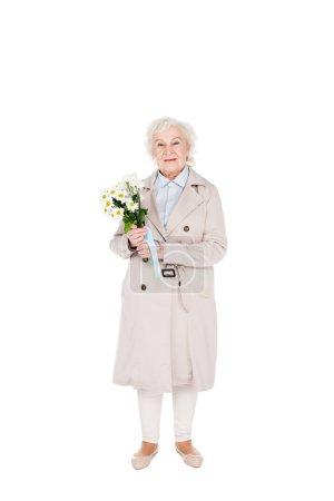 Photo pour Femme senior joyeuse tenant des fleurs en mains isolés sur blanc - image libre de droit