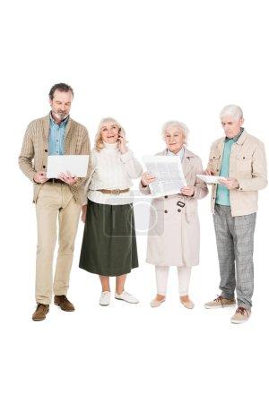 Senioren stehen mit Gadgets in der Nähe einer Frau, die Zeitung liest