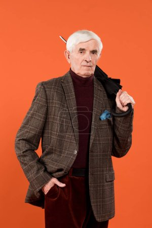 Photo for Trendy senior man holding umbrella while standing isolated on orange - Royalty Free Image